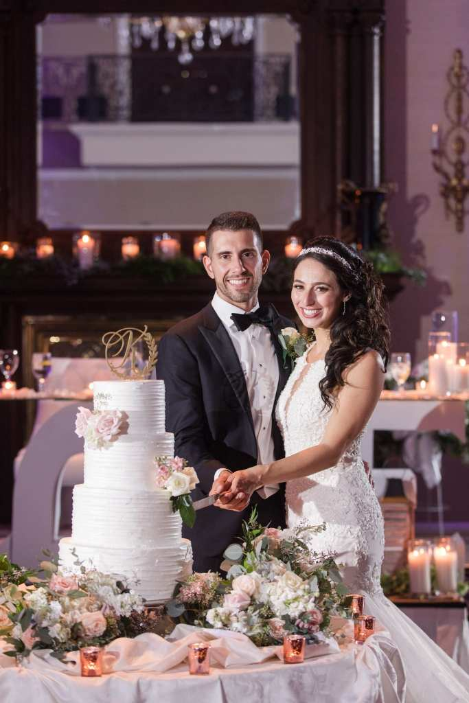 Formal portrait of the bride and groom cutting their four tier white wedding cake with floral accents by the Palace at Somerset Park