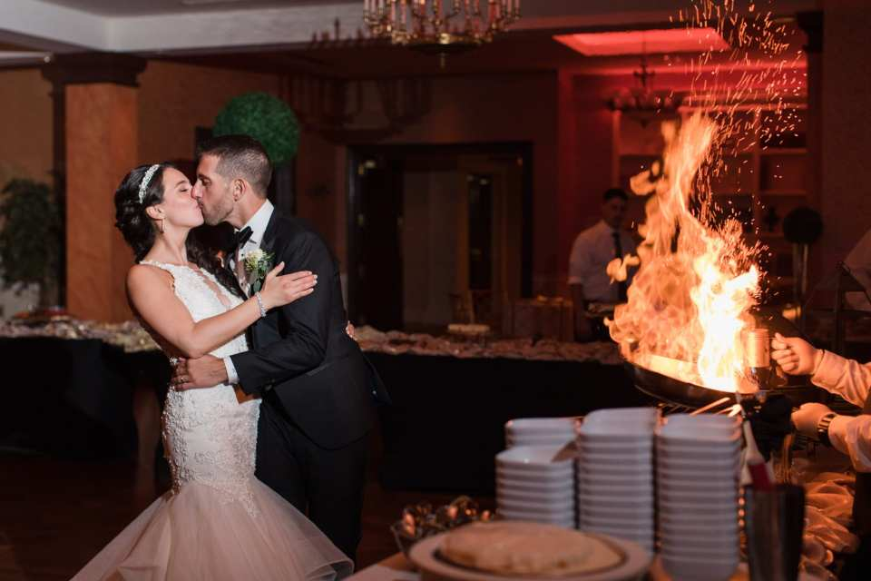 Groom slightly dipping the bride while kissing her while a chef flambe's on the right side of the photo inside the Palace at Somerset Park