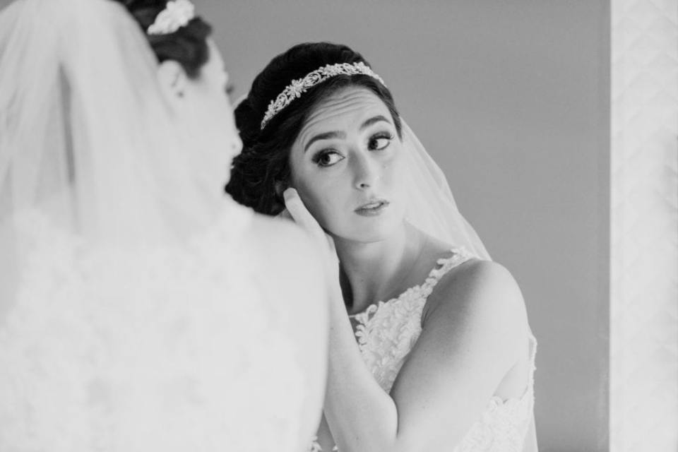 Black and white of the bride looking in the mirror as she puts in her earrings
