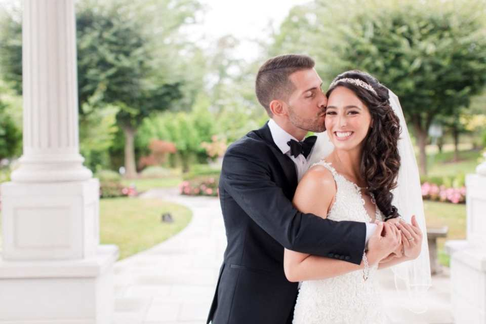 Bride looking at camera, smiling, with her grooms arms around her, while he is kissing her right temple