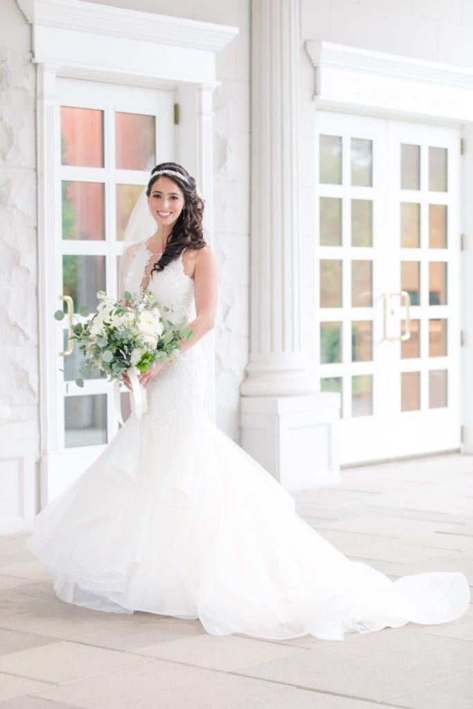 Formal bridal portrait of bride in her Maggie Sottero gown, holding her bridal bouquet by Jacqueline's Florist outside the Palace at Somerset Park
