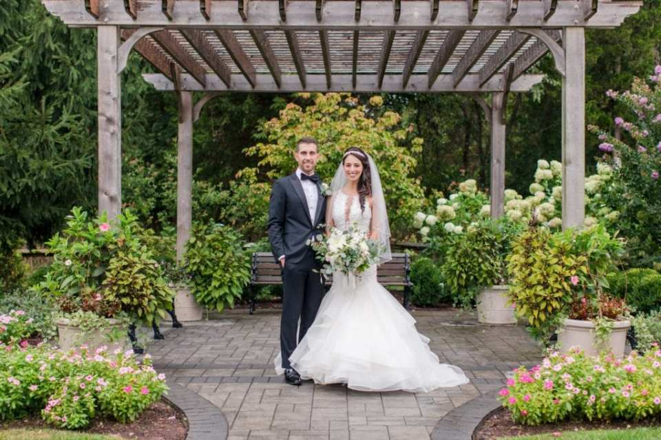 Formal portrait of the bride and groom on the grounds of the Palace at Somerset Park. Her gown by Maggie Sottero, his tuxedo by Enzo.