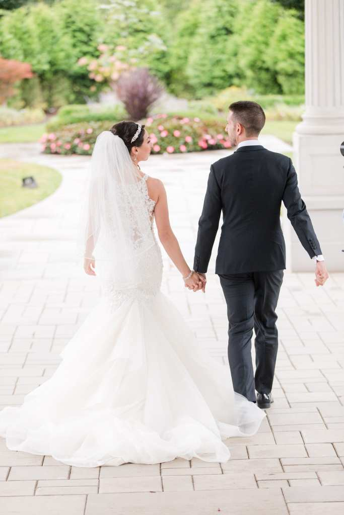 Bride and groom from behind, walking away from camera, holding hands, while looking at each other
