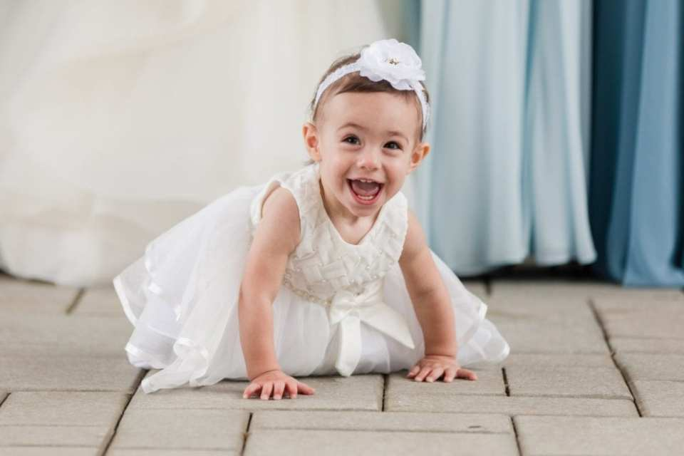 The flower girl on her hands and knees at the feet of the bridal party