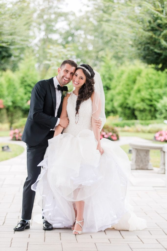 Fun portrait of the bride and groom outside of the Palace at Somerset Park, the bride lifting up her Maggie Sottero gown to show off her Jimmy Choo shoes
