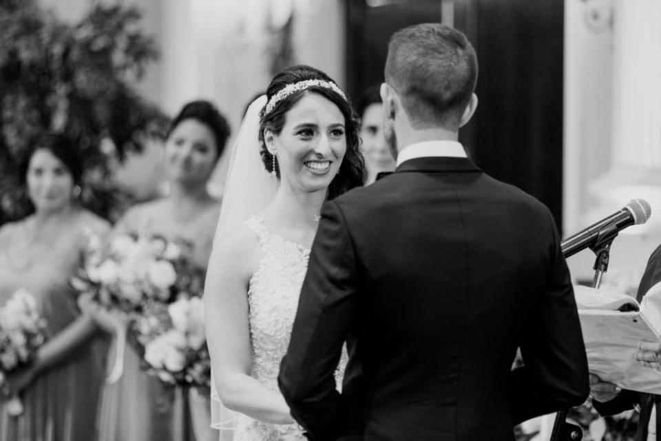 Black and white photo of the bride smiling during the wedding ceremony