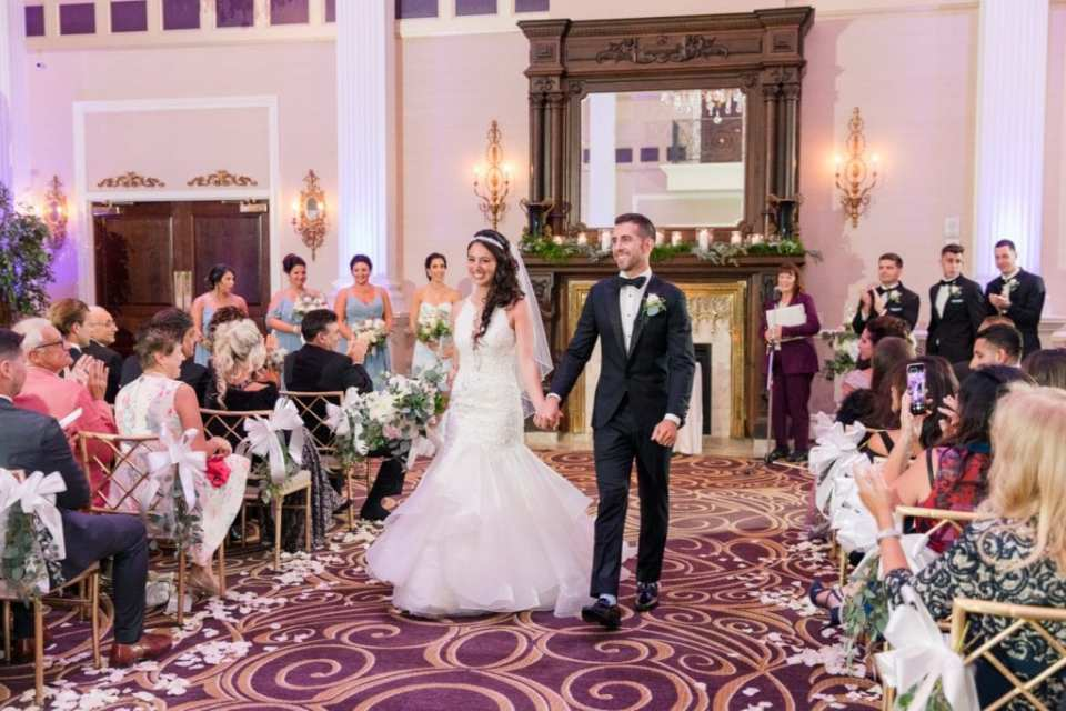 The bride and groom make their way down the aisle as husband and wife at the Palace at Somerset Park