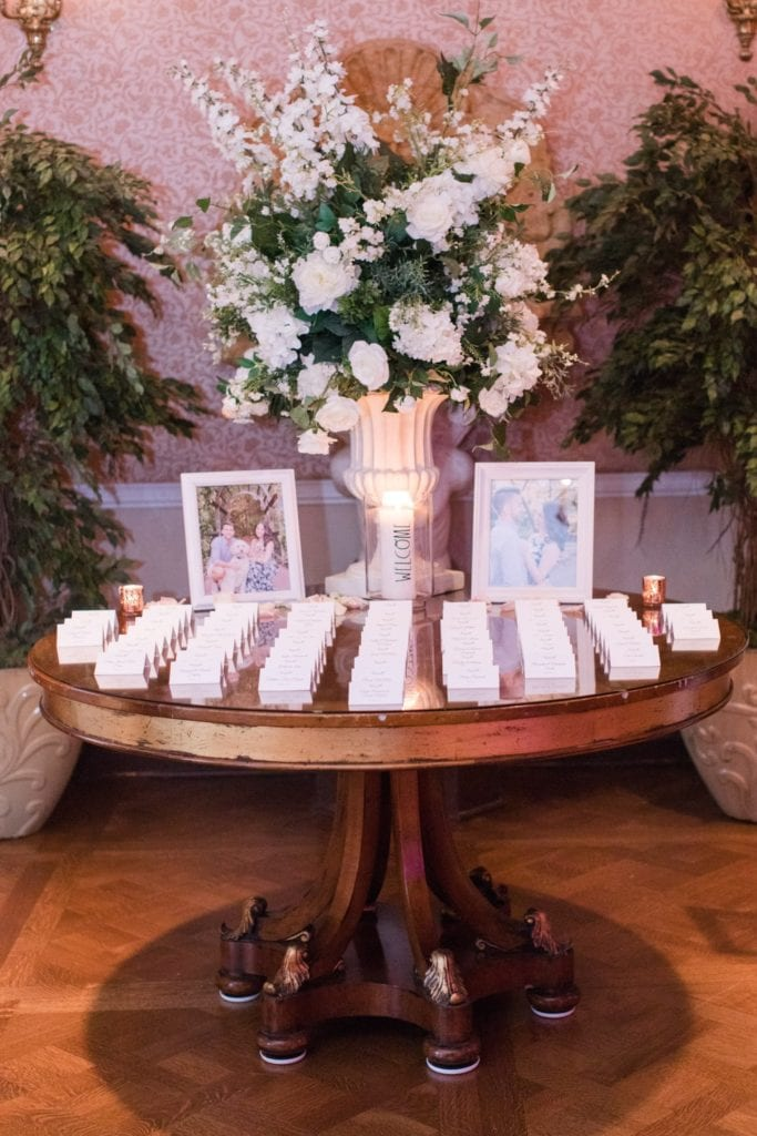 Wide angle photo of place card table decorated with florals and photos of the couple by Jaye Kogut Photography at the Palace at Somerset Park