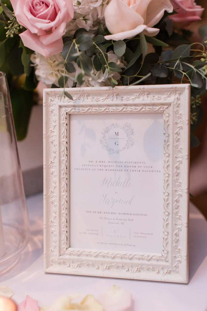Light blue and white wedding invitation framed and surrounded by blush florals by Jacquelines Florist