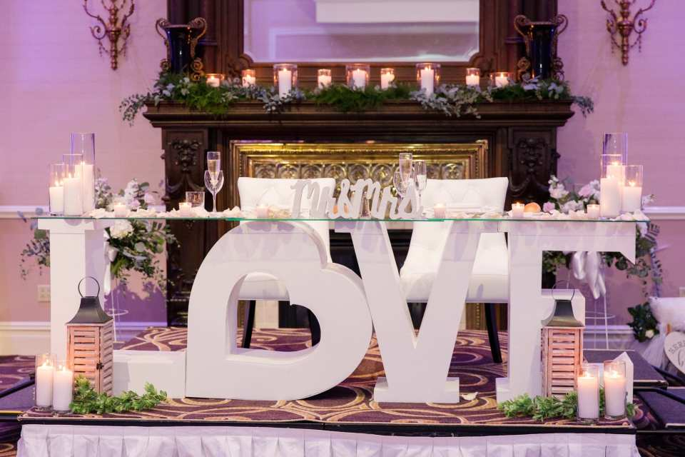 "Sweet heart table which is a wooden white table in the shape of the word LOVE the ""O"" in the shape of a heart, surrounded by candles at the Palace at Somerset Park"