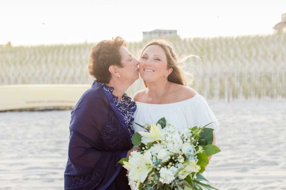 The bride gets a kiss on the cheek from her mother