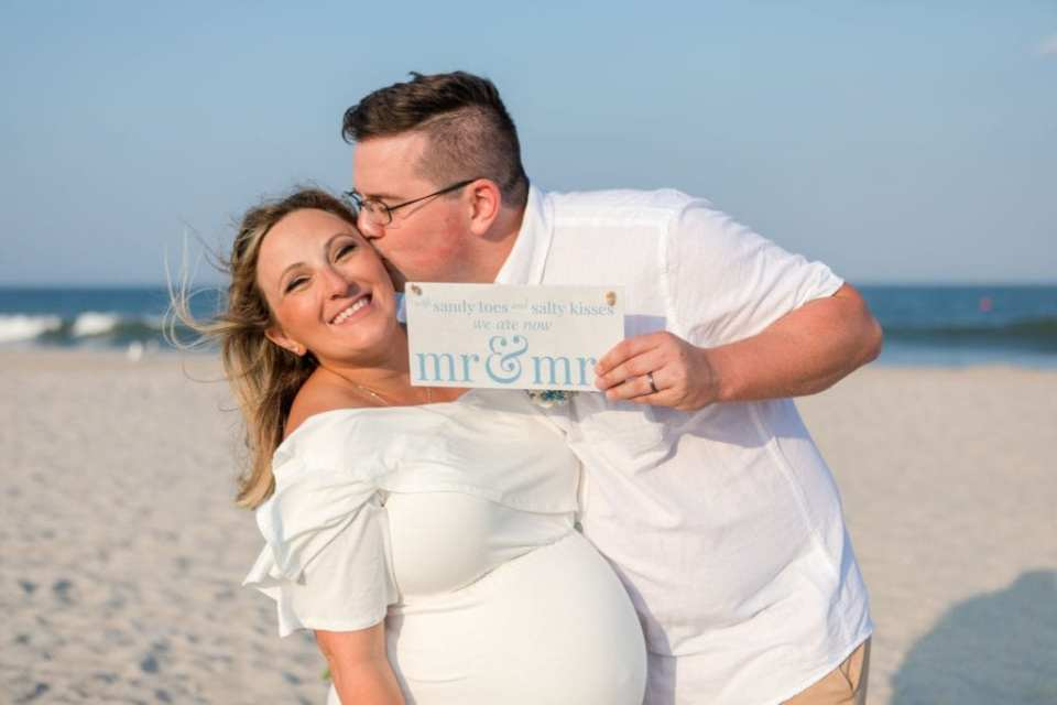 Groom leaning his new wife over, kissing her cheek, while holding a personalized Mr. and Mrs. sign after their Lavallette Beach elopement
