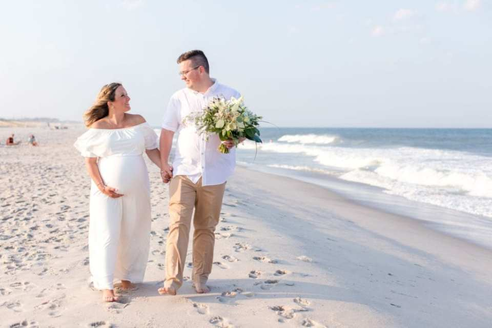 Bride in her off the shoulder white gown, groom in his khakis and short sleeve white button down shirt walking hand in hand on Lavallette Beach, he is holding her bridal bouquet