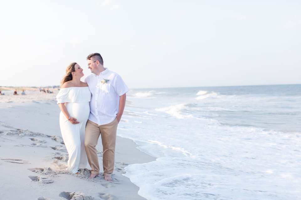 Bride and groom side by side, arms wrapped around each others waist, looking at one another, amongst the waves on Lavallette Beach