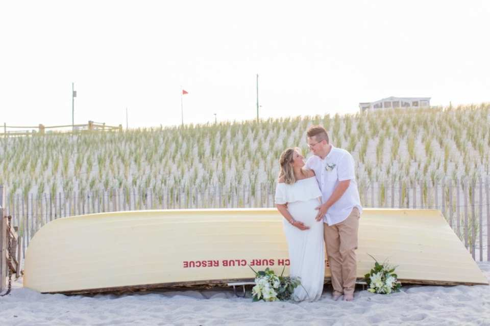 Bride and groom side by side, arms wrapped around each others waist, looking at one another, each with a hand on her belly, in front of a rescue boat on the beach in Lavallette New Jersey