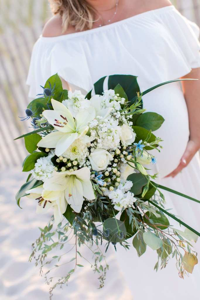 bride holding her bouquet of various white florals in various greens