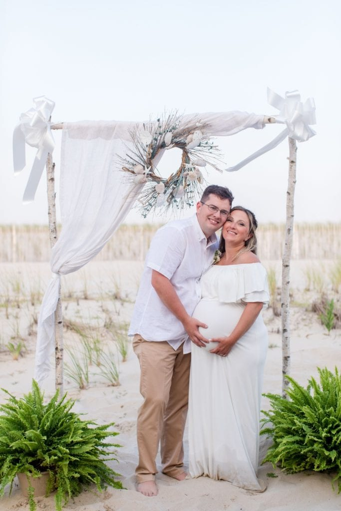 bride and groom pose under white birch and fabric altar set up on the beach in Lavallette, New Jersey