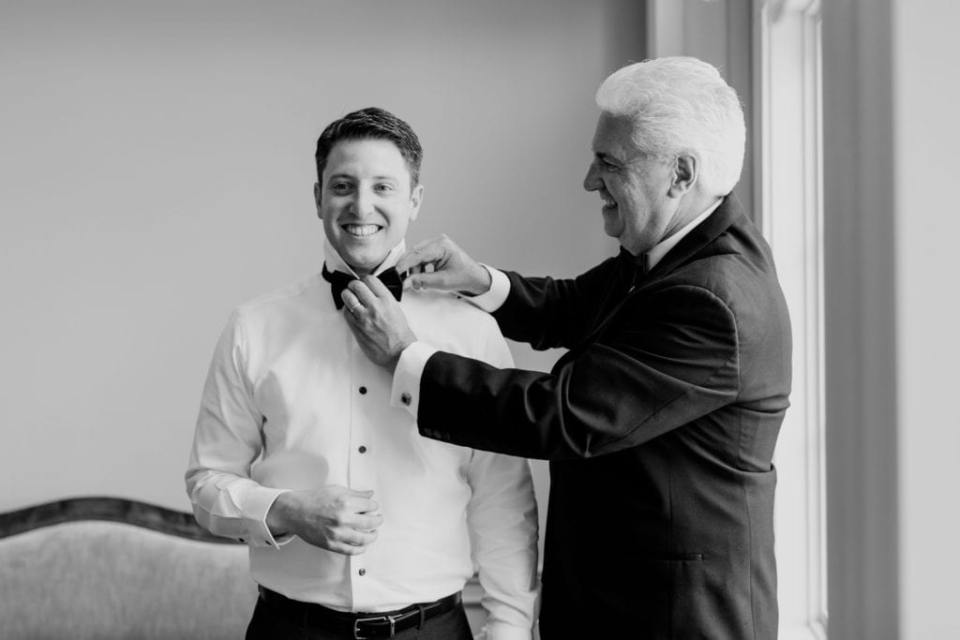 Black and white candid photo of the groom being helped with his bowtie by his father