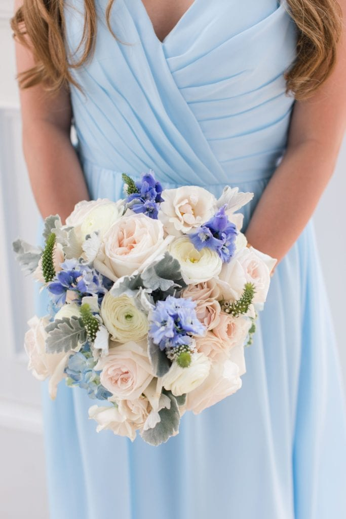 Close up of bridesmaids bouquet with off white and blue florals, with a touch of greens by Crest Florist