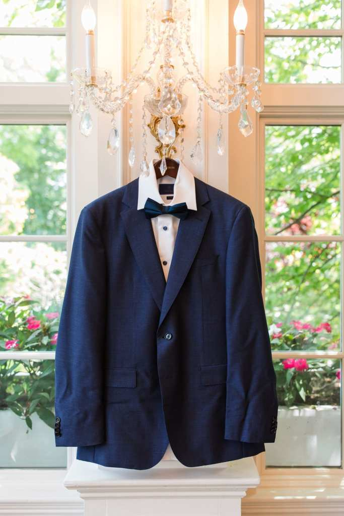 The grooms custom Hugo Boss navy blue tuxedo hanging on a crystal chandelier wall sconce