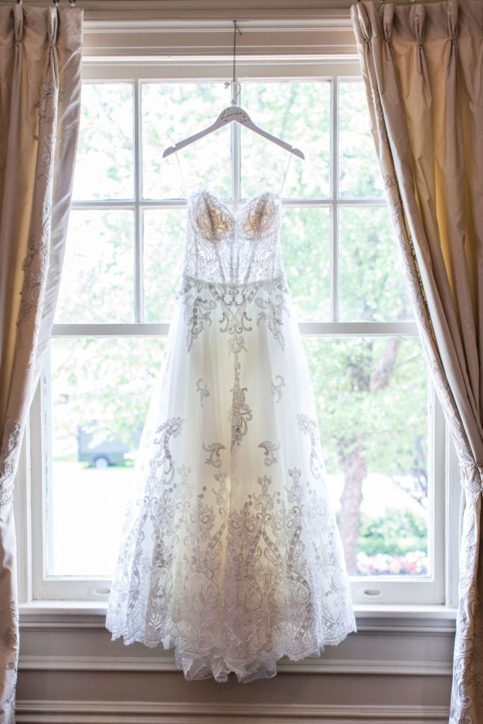 Brides Maggie Sottero gown hanging on a wooden hanger in a window at the Park Savoy Estate