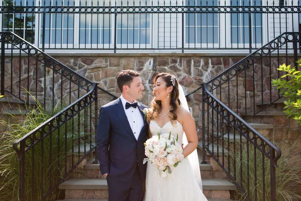 The bride and groom, side by side, stand at the bottom of the stairs for their Park Savoy Estate wedding photos