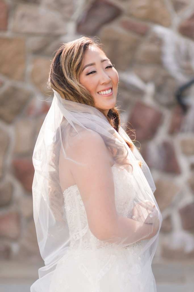 Side view of the bride, who is looking and smiling towards the camera, with her veil wrapped around her