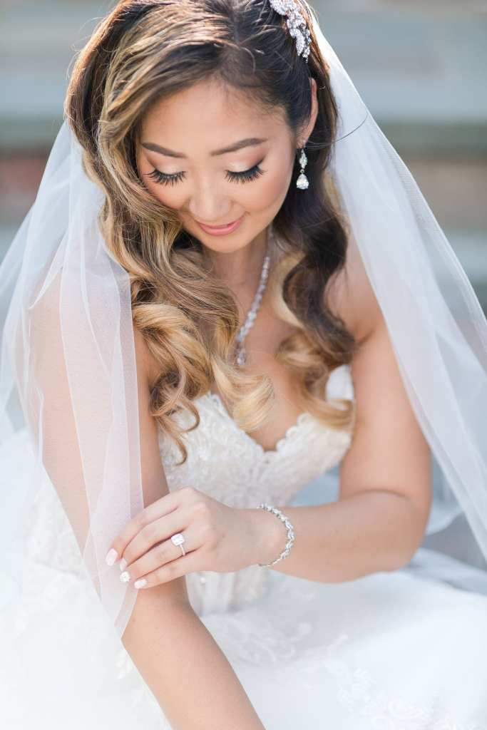 Portrait of the bride sitting, her veil wrapped slightly around her, her looking down towards her left hand, hair and makeup by The Glam Team