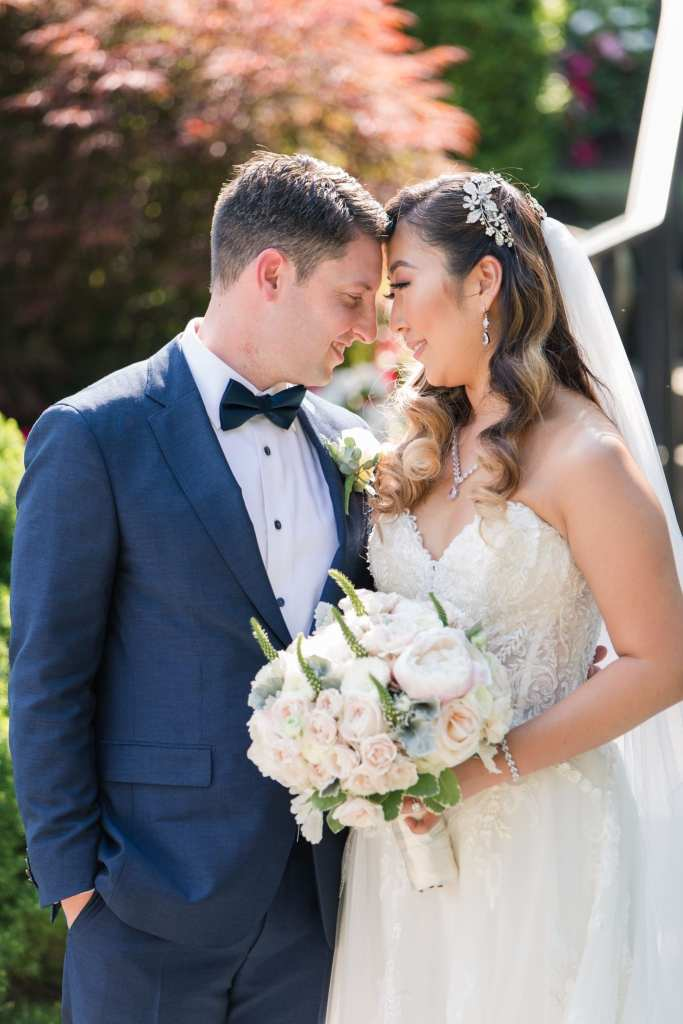 3/4 shot of the bride and groom forehead to forehead, her bouquet of white flowers by Crest Florist