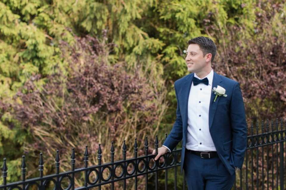 Candid photo of the groom outdoors, looking off into the distance
