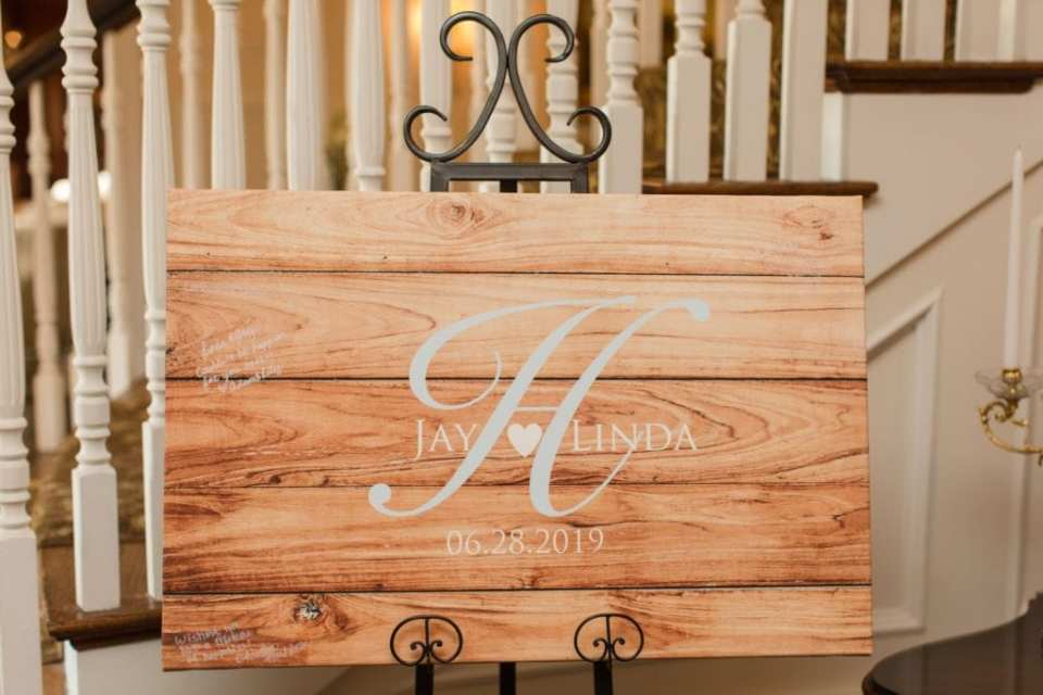 Wooden guest plaque with the couples names and date of wedding on display