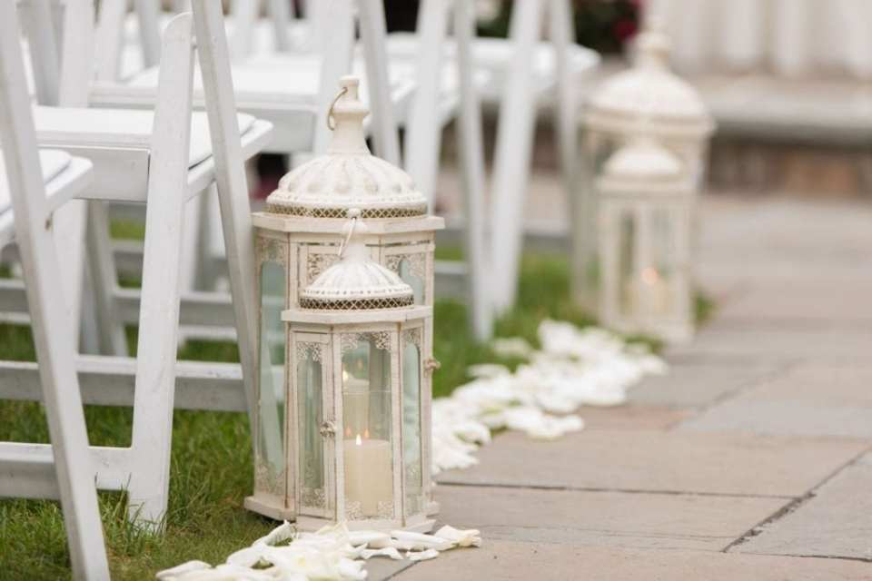Wedding ceremony details: ivory candle lanterns and rose petals adorning the aisle