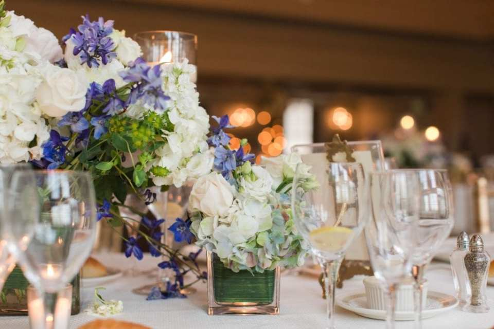 Close up of small florals in square votive type vases scattered about the table in the reception room by Petals Florist