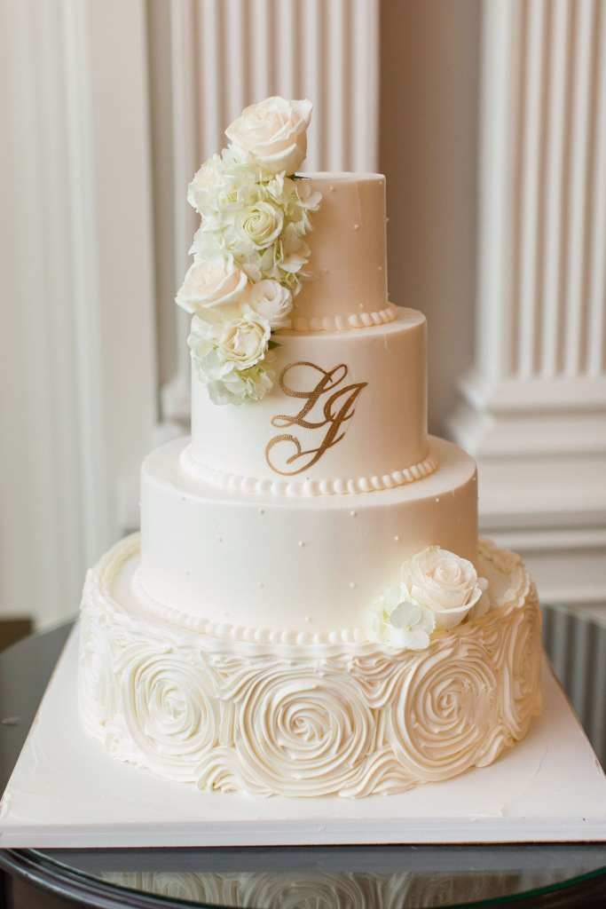 Formal photo of the off white four tier wedding cake, each tier decorated slightly differently, white florals adorn two tiers just slightly, and the bride and grooms initials in gold appear on the second tier, by Palermo's Bakery