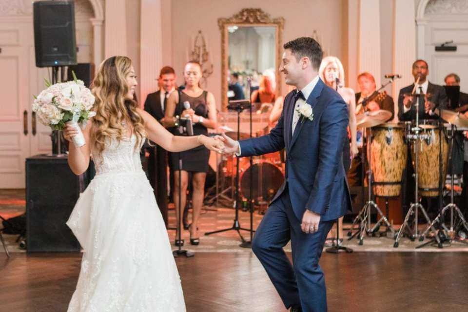 The groom leads his bride onto the dance floor to begin their first dance after they made their entrance into the wedding reception. The Jellyroll Band is in the background