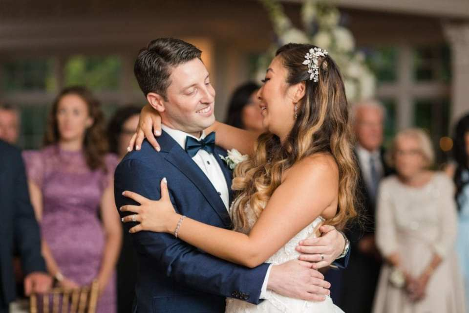 The bride and groom smile at one another during their first dance as husband and wife