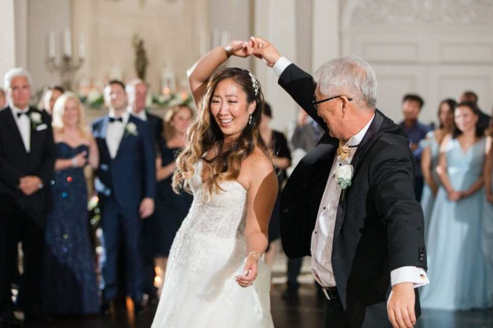 The father of the bride twirls the bride during their traditional father daughter dance