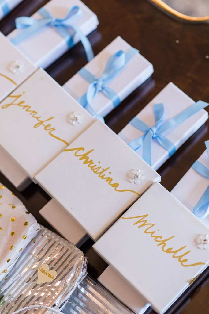 Gifts for the wedding party in white boxes with blue ribbon and gold lettering displayed