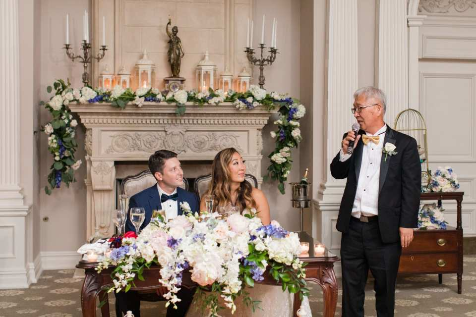 The father of the bride stands next to the sweetheart table, where the couple sits, and makes a speech during the wedding reception