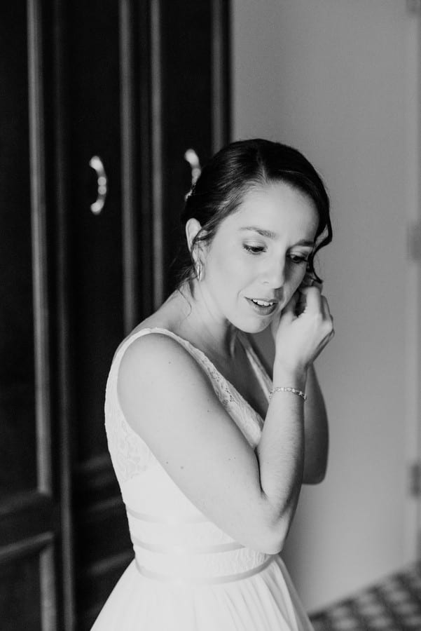 Black and white photo of the bride putting in her earrings