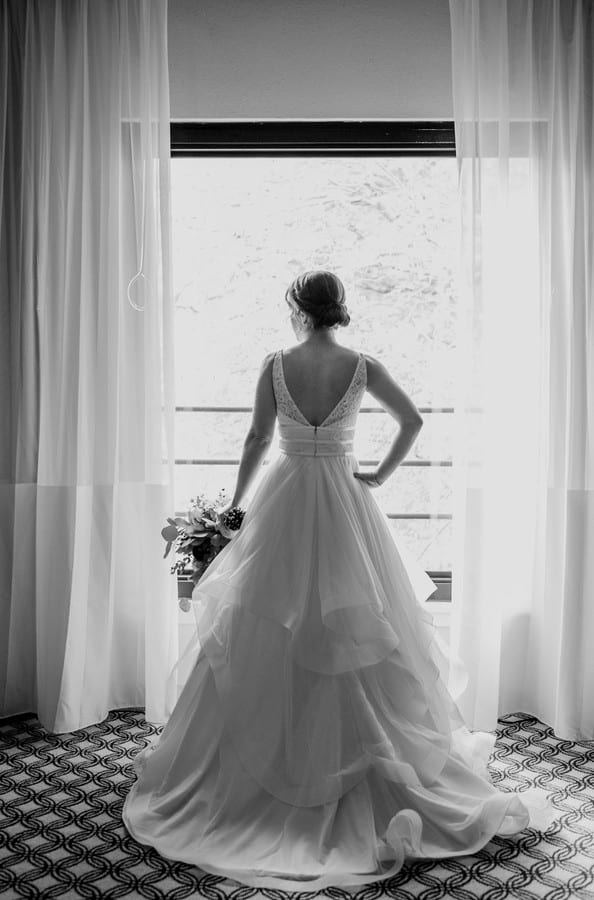 Black and white full length photo of the bride from behind, gazing out a window. Gown by Mikaella Bridal