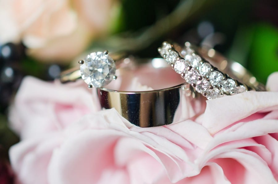 Close up of the round diamond solitaire engagement ring and all wedding rings, both his and her diamond bands