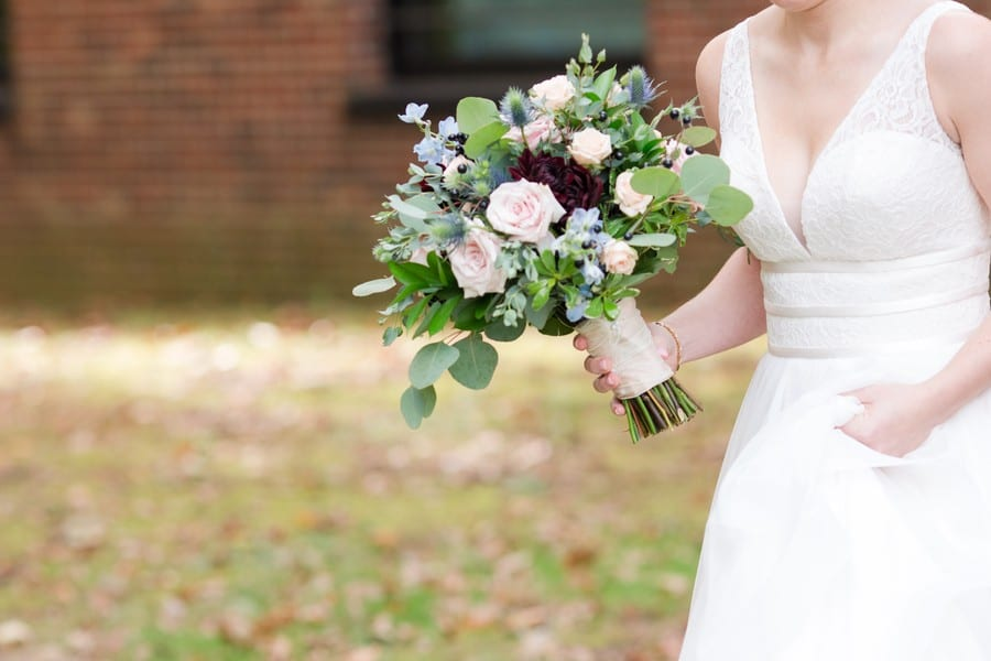A 3/4 shot of the bride, her Mikella Bridal gown details in view, along with her bridal bouquet of greens, blush, burgundy and blue florals by Petal Pushers
