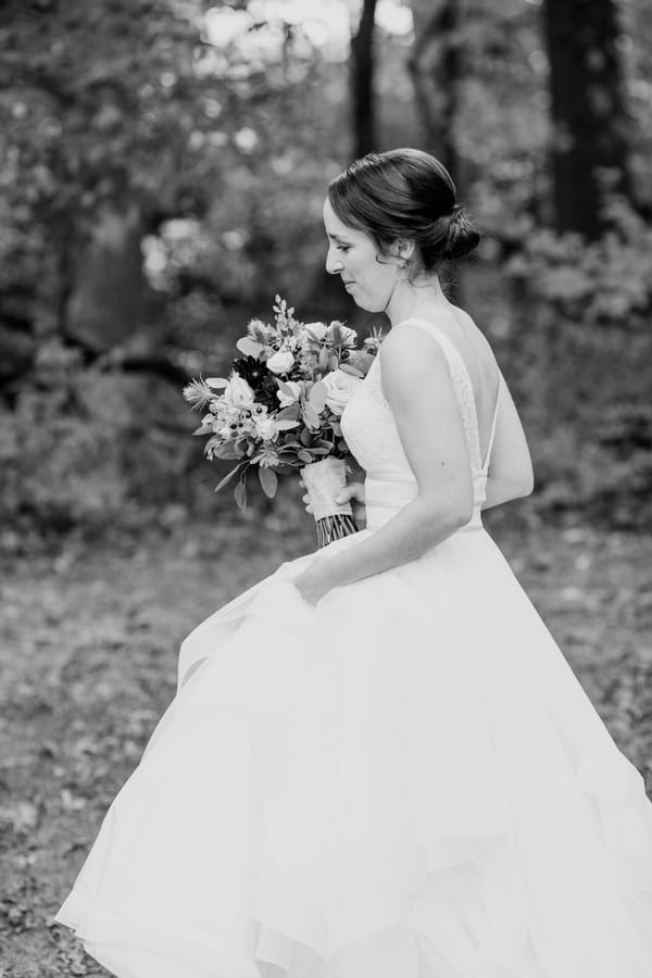 Black and white side portrait of the bride as she walks towards her groom for their first look