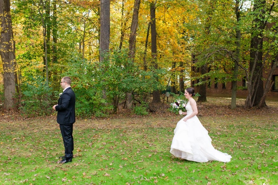 The first look outdoors as the bride is walking up behind her groom