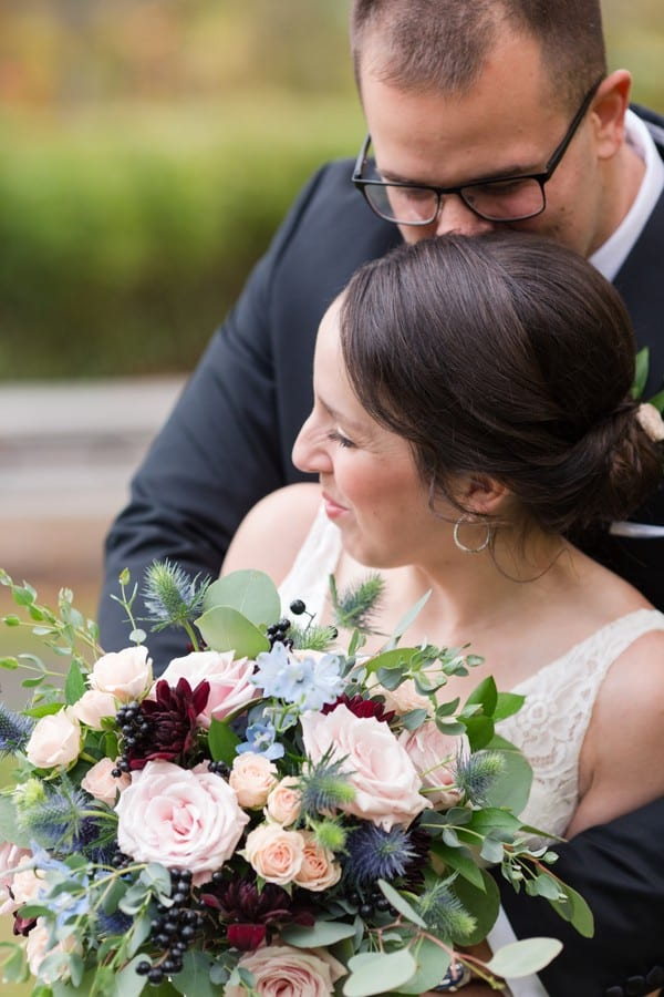 A close up, from above, of the groom kissing his brides temple while she looks down. Her bouquet by Petal Pushers in full view