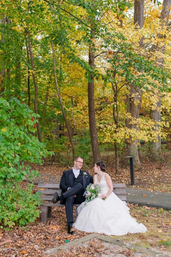 Portrait of the bride and groom sitting on a wooden bench in the fall foliage