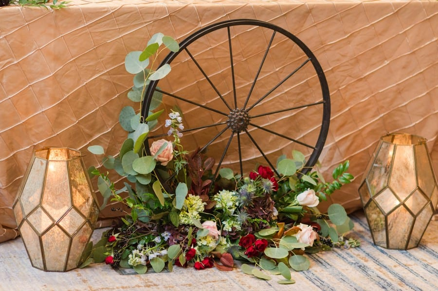 Close up of the details of the sweetheart table by Petal Pushers with a light gold patterned table covering, unique multicolored candle holders, various florals and a wagon wheel