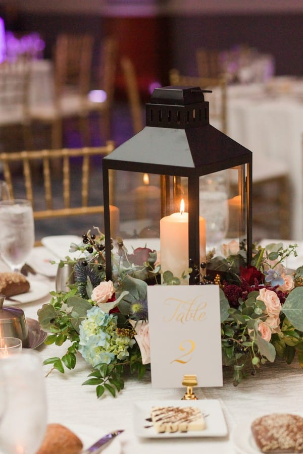 Wedding details: black and clear candle holder surrounded by florals and greens on a reception table by Petal Pushers at the Princeton Marriott at Forrestal wedding