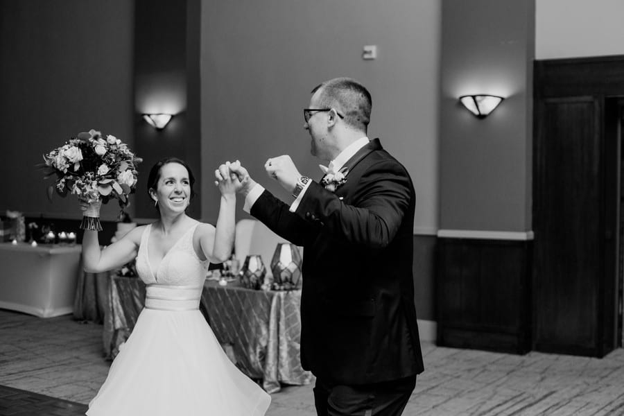 Black and white candid photo of the bride and groom entering their wedding reception